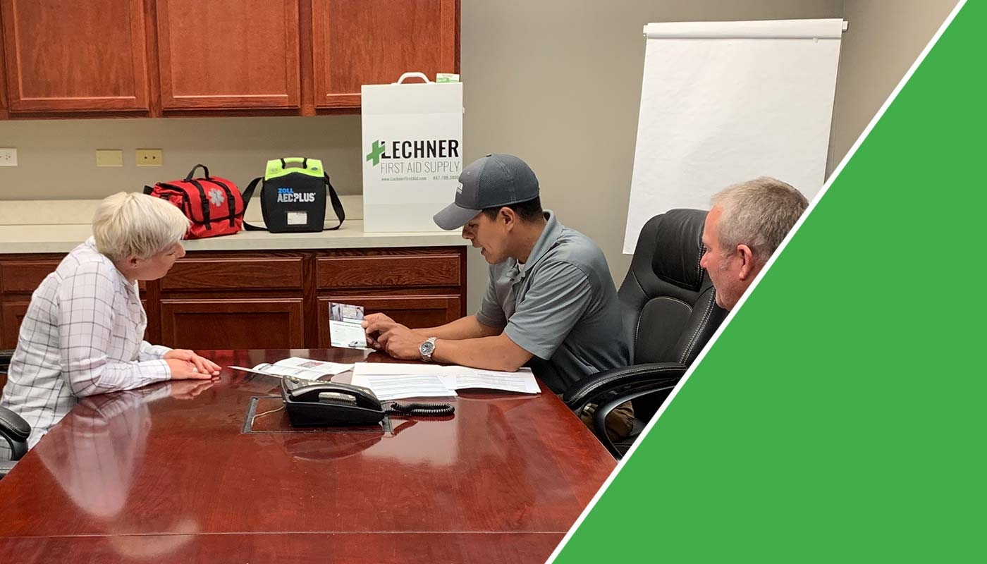 Lechner First Aid Sales Representatives discussing the benefits of a Lechner First Aid Program/ First Aid Service with a business owner.
