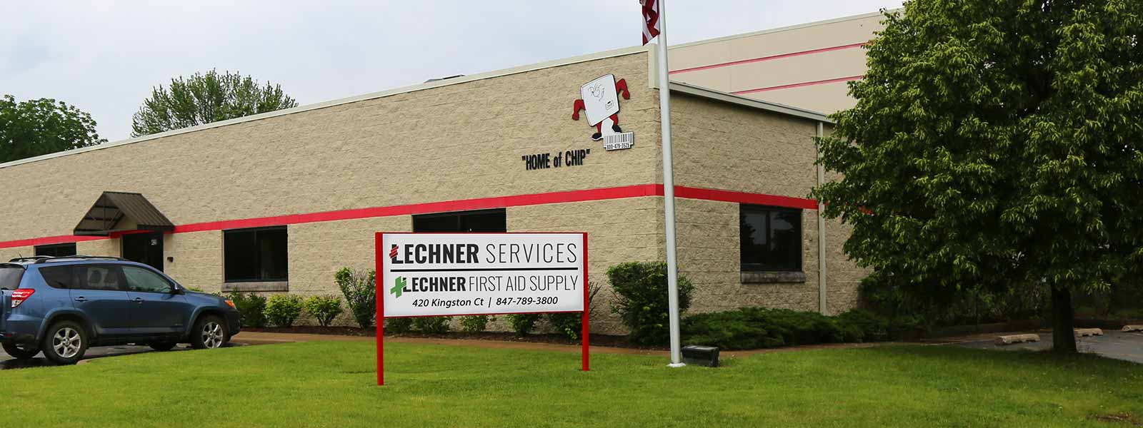 The outside of Lechner First Aid and Uniform Services brick building with a Lechner Services sign in the front yard.