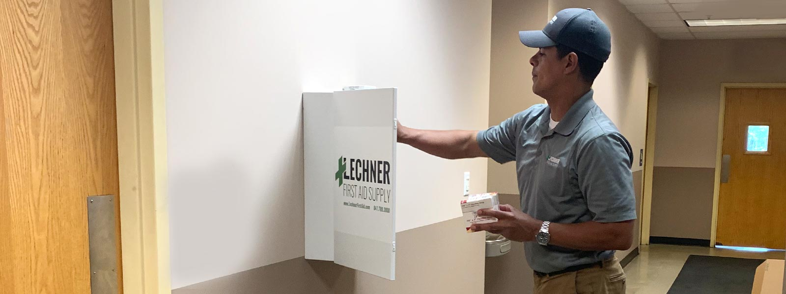 Lechner First Aid Sales Representative putting first aid supplies and ppe in a First Aid cabinet.