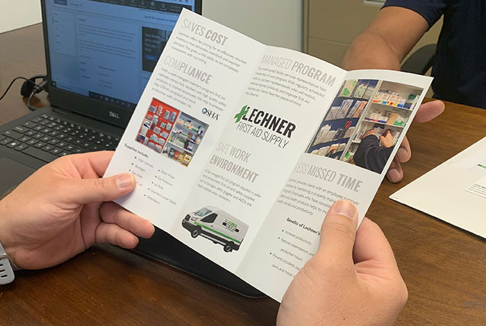 A Lechner First Aid Sales Representative holding a Lechner First Aid Supply Brochure.