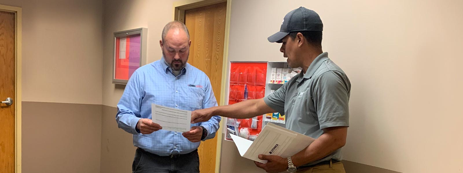 Lechner First Aid Sales Representatives discussing the benefits of a Lechner First Aid Program/ First Aid Service with a safety manager.