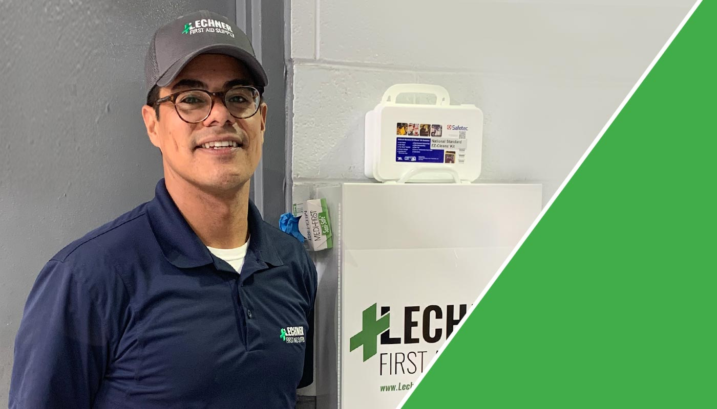 A Lechner First Aid Sales Representative standing by a Lechner First Aid kit/First Aid cabinet.